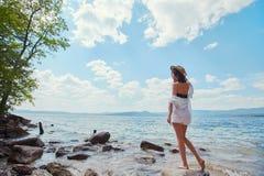 En spenslig kvinna i en vit skjorta och hatt kopplar av nära vattnet arkivbild