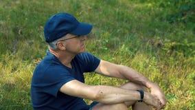 En spensliga allvarlig gråhårig man i en blå t-skjorta, lock och exponeringsglas sitter på det gröna gräset i skogen på en sommar lager videofilmer