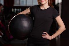En sportflicka med en svart boll fotografering för bildbyråer
