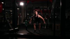 En sportidrottsman nen i idrottshallen lyfter stången med en vikt ovanför hans huvud från sammanträdepositionen arkivfilmer