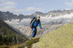 En sportig alpinist klättrar en bergtoppmöte framme av glaciärer Royaltyfria Foton