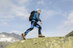 En sportig alpinist klättrar en bergtoppmöte i de schweiziska fjällängarna Royaltyfri Foto