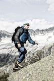 En sportig alpinist klättrar en bergtoppmöte i de schweiziska fjällängarna Arkivbilder