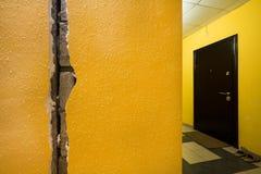 En spricka i väggen av hyreshusen Gul vägg i ingången Arkivbild