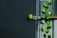 En spridning av gröna rå segment av broccoli på en exponeringsglasplatta Sund ätamodell på en svart bakgrund kopiera avstånd royaltyfria foton