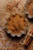 En spridning av kanel i plåtar och kanelbruna pinnar på en texturerad bakgrund med textiler under säckväven royaltyfri bild