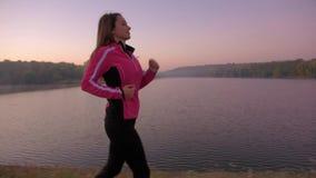 En spring för ung kvinna på sjön på soluppgång stock video