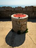 En springbrunn ut ur stenen med ett rött lock arkivbild