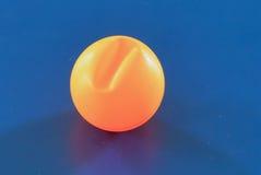 En sprucken apelsin knackar pongbollen royaltyfria bilder