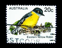 En stämpel som skrivs ut i Australien, visar en bild av den östliga gula rödhakefågeln på värde på cent 20 Royaltyfria Foton