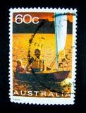 En stämpel som skrivs ut i Australien, visar en bild av en fader och en son på segelbåten på värde på cent 60 arkivbild