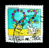 En stämpel som skrivs ut i Australien, visar en bild av tecknad filmsymbolsföreställningskonst för att bo tillsammans stämpelseri Royaltyfri Bild