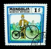 En stämpel som skrivs ut i Mongoliet, visar en bild av a-mannen med den klassiska cykeln för stora hjul Royaltyfria Foton