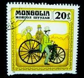 En stämpel som skrivs ut i Mongoliet, visar en bild av a-manridningen på en klassisk cykel för stora hjul Royaltyfri Foto