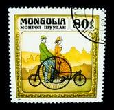En stämpel som skrivs ut i Mongoliet, visar en bild av en parridning på en klassisk cykel för stora hjul Arkivbild