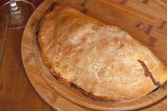 En stängd italiensk pizzacalzone på en träplatta Royaltyfria Bilder