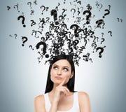 En stående av brunetten med förhöruttrycks- och frågefläckar ovanför hennes huvud arkivbild