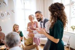 En stående av den multigeneration familjen med gåvor på ett inomhus födelsedagparti arkivbilder