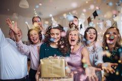 En stående av den multigeneration familjen med gåvor på ett inomhus födelsedagparti royaltyfria foton