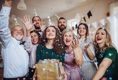 En stående av den multigeneration familjen med gåvor på ett inomhus födelsedagparti fotografering för bildbyråer