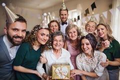 En stående av den multigeneration familjen med gåvor på ett inomhus födelsedagparti arkivfoton