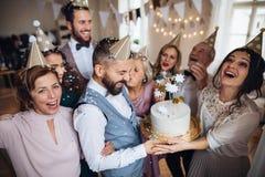 En stående av den multigeneration familjen med en kaka på ett inomhus födelsedagparti arkivfoton
