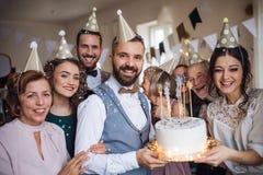 En stående av den multigeneration familjen med en kaka på ett inomhus födelsedagparti royaltyfria foton
