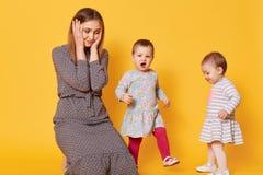 En stående av den stressade trötta modern, som täcker hennes öron med två händer från unges höga ropa, lider från fruktansvärd hu arkivfoton