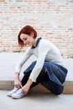 En stående av den unga affärskvinnan som utomhus som sitter binder skosnöre royaltyfri bild