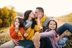 En stående av den unga familjen med två småbarn i höstnatur på solnedgången som kysser arkivbilder