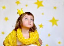 En stående av en fundersam liten flicka i en gul halsduk och med en krona på henne hade Royaltyfri Foto