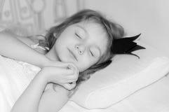 En stående av en sova liten flicka med en krona på hennes huvud arkivfoto