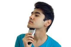 En stående av en ursnygg ung man som står åt sidan och rakar Fotografering för Bildbyråer