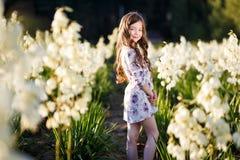 En stående av ett långt hår för gullig liten girlwith i yttersida på solnedgången i fältet av vita palmliljablommor som har gycke arkivfoton