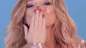 En stående av en härlig ung kvinna som blåser en kyss på kameran och leendena Bakgrunden är blått stock video