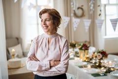 En stående av en hög kvinna som inomhus står i en rumuppsättning för ett parti arkivbild