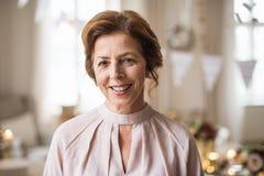 En stående av en hög kvinna som inomhus står i en rumuppsättning för ett parti royaltyfri fotografi