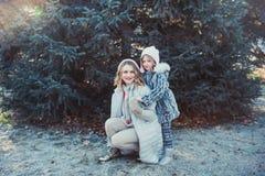 En stående av en lycklig familj: en ung härlig kvinna med hennes lilla gulliga dotter som går i vinterstaden, parkerar arkivbild