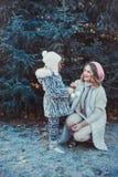 En stående av en lycklig familj: en ung härlig kvinna med hennes lilla gulliga dotter som går i vinterstaden, parkerar royaltyfri bild