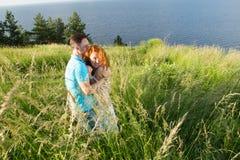 En stående av lyckliga härliga par på naturen med den stora sjön Barnpar som kramar på banken av floden Man som kramar den röda h royaltyfri foto