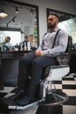 En stående av en stilfull man på frisersalongbakgrund Stilig grabb med en ny frisyr Stil modebegrepp royaltyfri fotografi