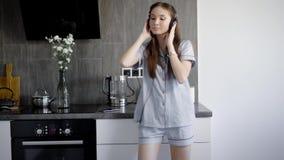 En stående av en ung dam, som tycker om musik från hörlurar, en söt dam sjunger och dansar till kraftig musik arkivfilmer