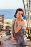 En stående av en ung elegant flicka borrade languidly på havet Royaltyfri Bild