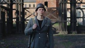 En stående av en ung stilig tysk soldat som lyfter hans huvud En koncentrationslägerrekonstruktion på bakgrunden stock video