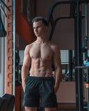 En stående av en ung styrkaidrottsman nen i en idrottshall Definierad idrottsman nen med stora muskler royaltyfria foton