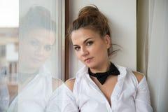 En stående för ` s för ung kvinna med en svart fluga Arkivfoto