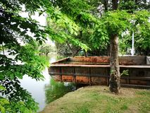 En stålpråm som fylls med regnvatten och sidor, på banken av thailändsk frodig gräsplan, parkerar högt sjön för ` s Fotografering för Bildbyråer