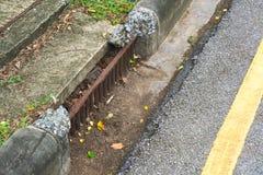 En ståltrottoarkantdränering, det har eroderat utöver reparation, på en gata, i ett land som ser tunga regniga säsonger arkivfoto