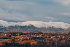 En stad i Skottland tände vid solnedgångljus på en bakgrund av snöig montain Royaltyfri Foto