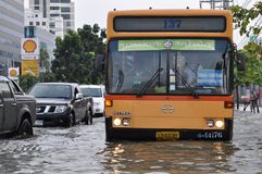 En stadsbuss håller servicen på i en översvämmad gata av Bangkok på 05. November 2011 Royaltyfri Bild